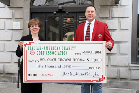 Jack Munella Jr., chair of the Italian American Charity Golf Association, presents a check in the amount of $50,000 to Betsy Wright, WCA Hospital president/CEO, representing the proceeds from the Italian American's 2013 fundraising activities and the first installment of a three-year, $150,000 pledge to enhance local cancer care at WCA Hospital through the purchase of a Fluoroscopic C-Arm.